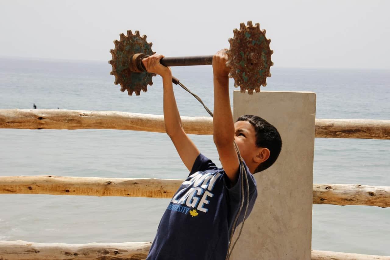 Un enfant en pleine séance de musculation