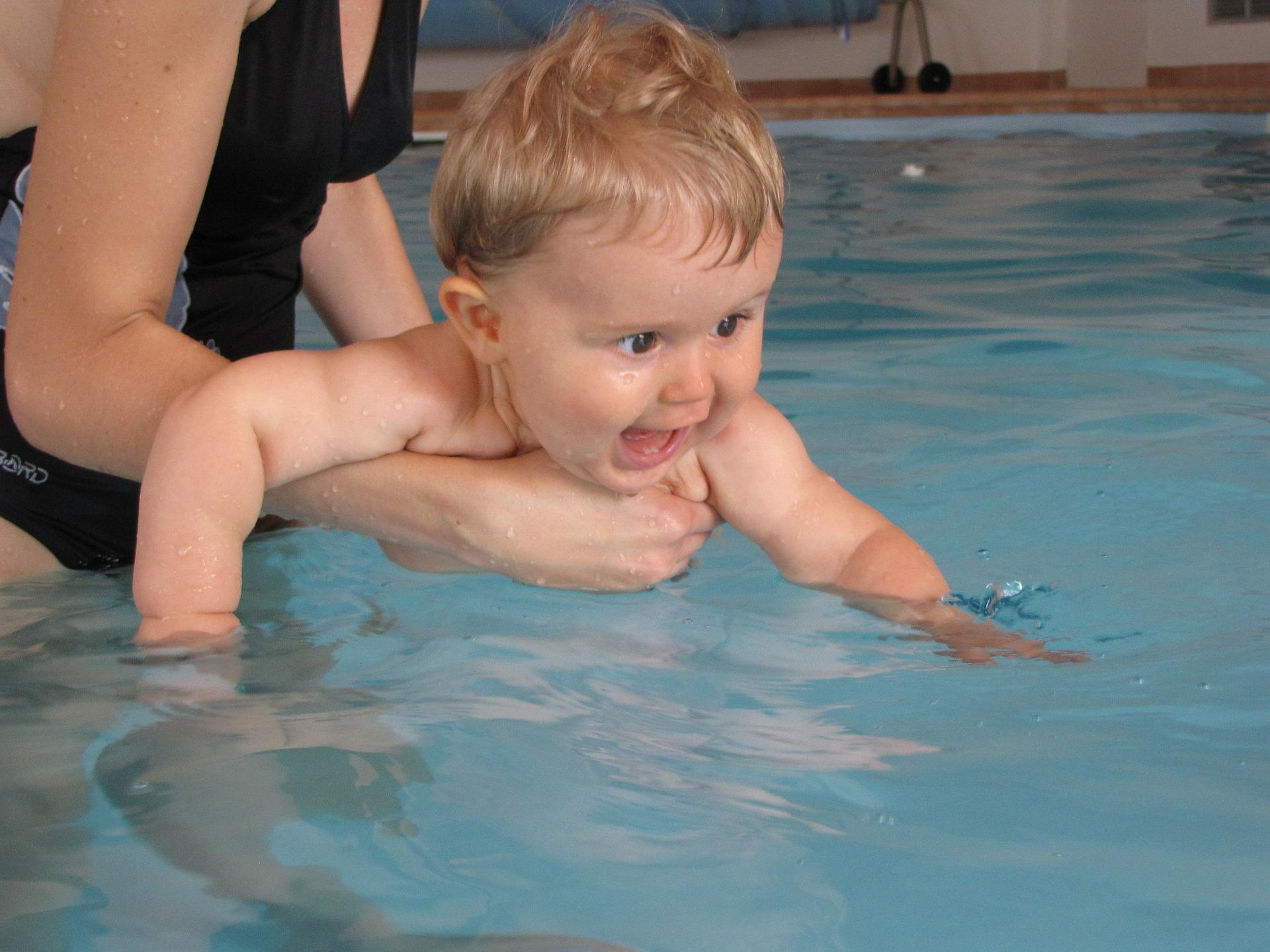 Un bébé qui apprend à nager dans une piscine avec sa maman