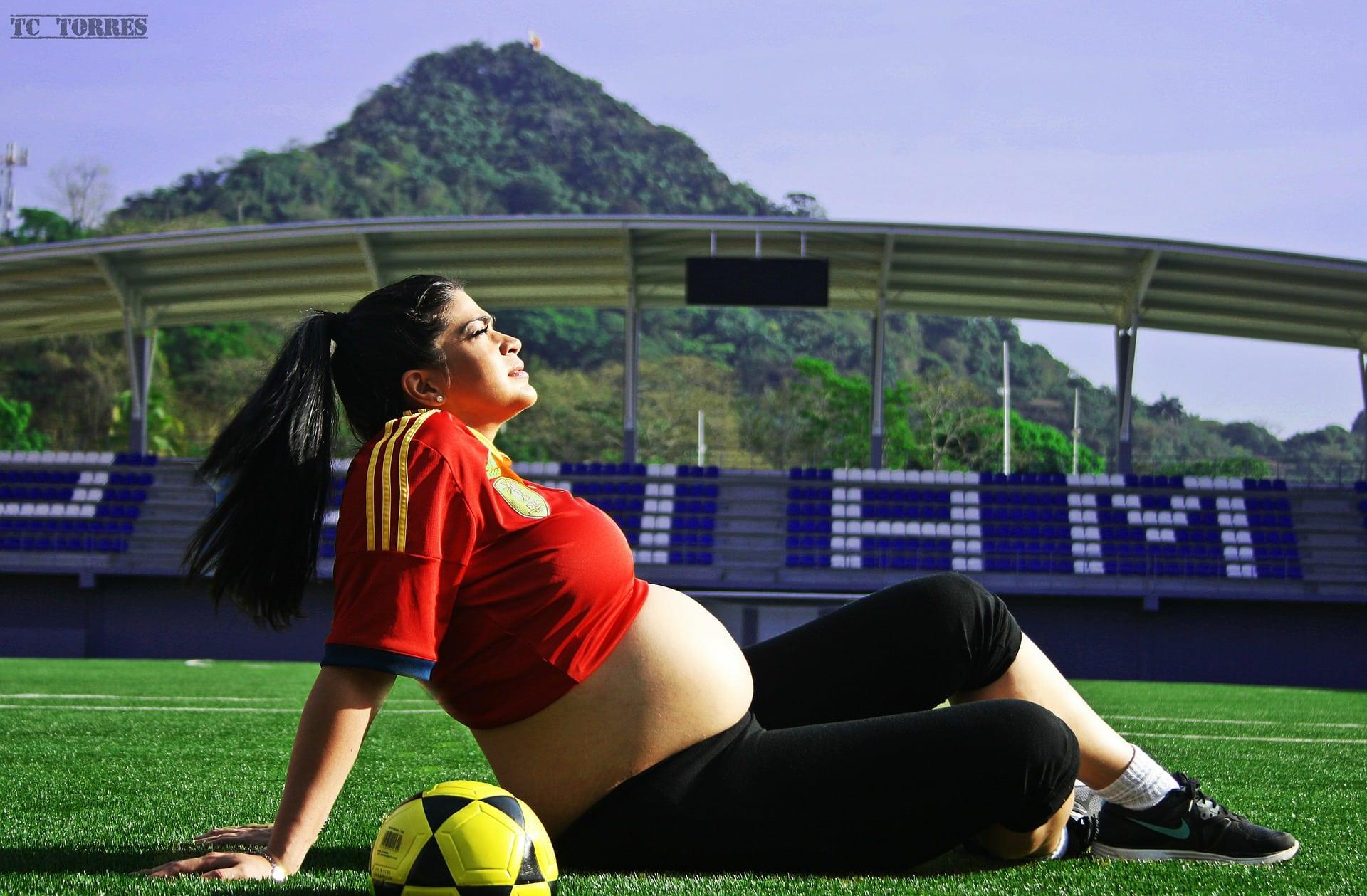 Femme enceinte qui joue au football