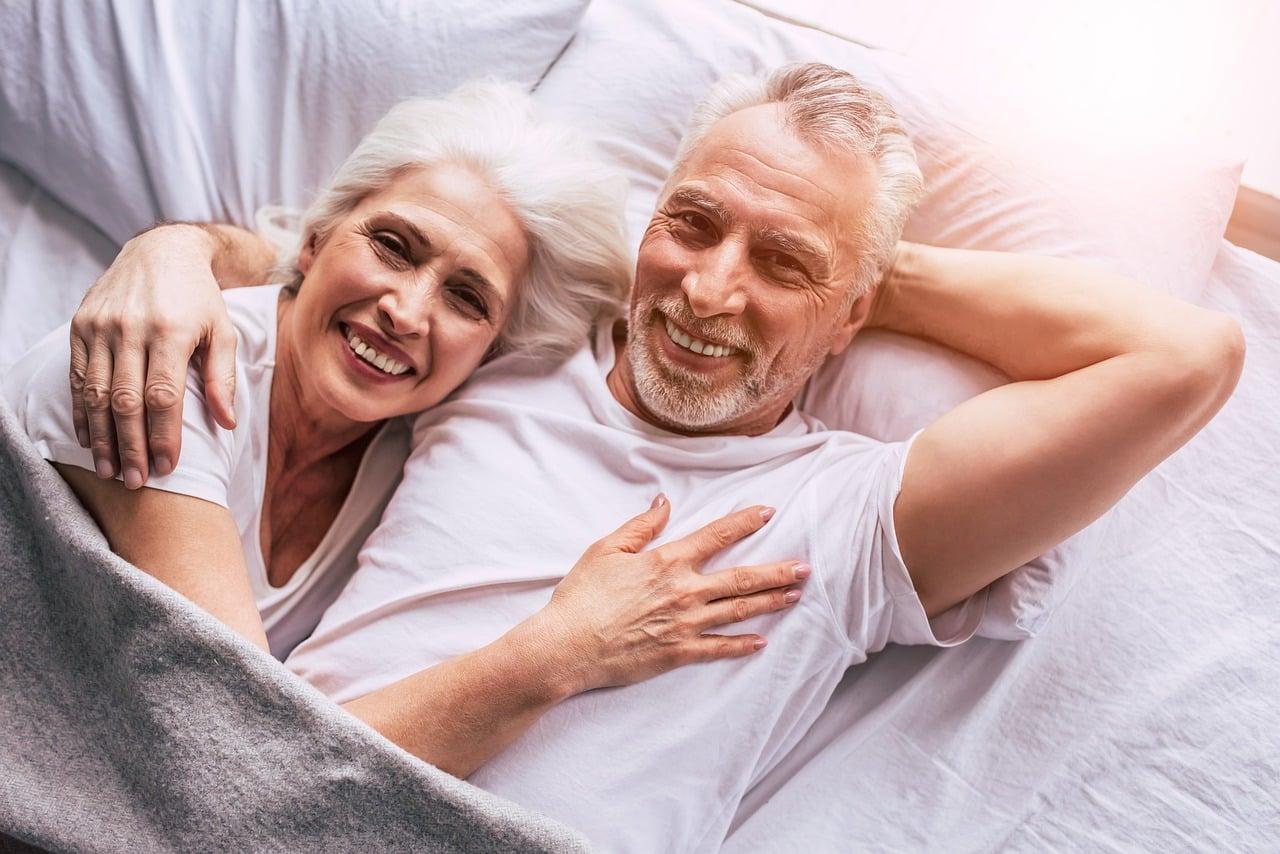 Couple de senior dans un lit après avoir fait l'amour