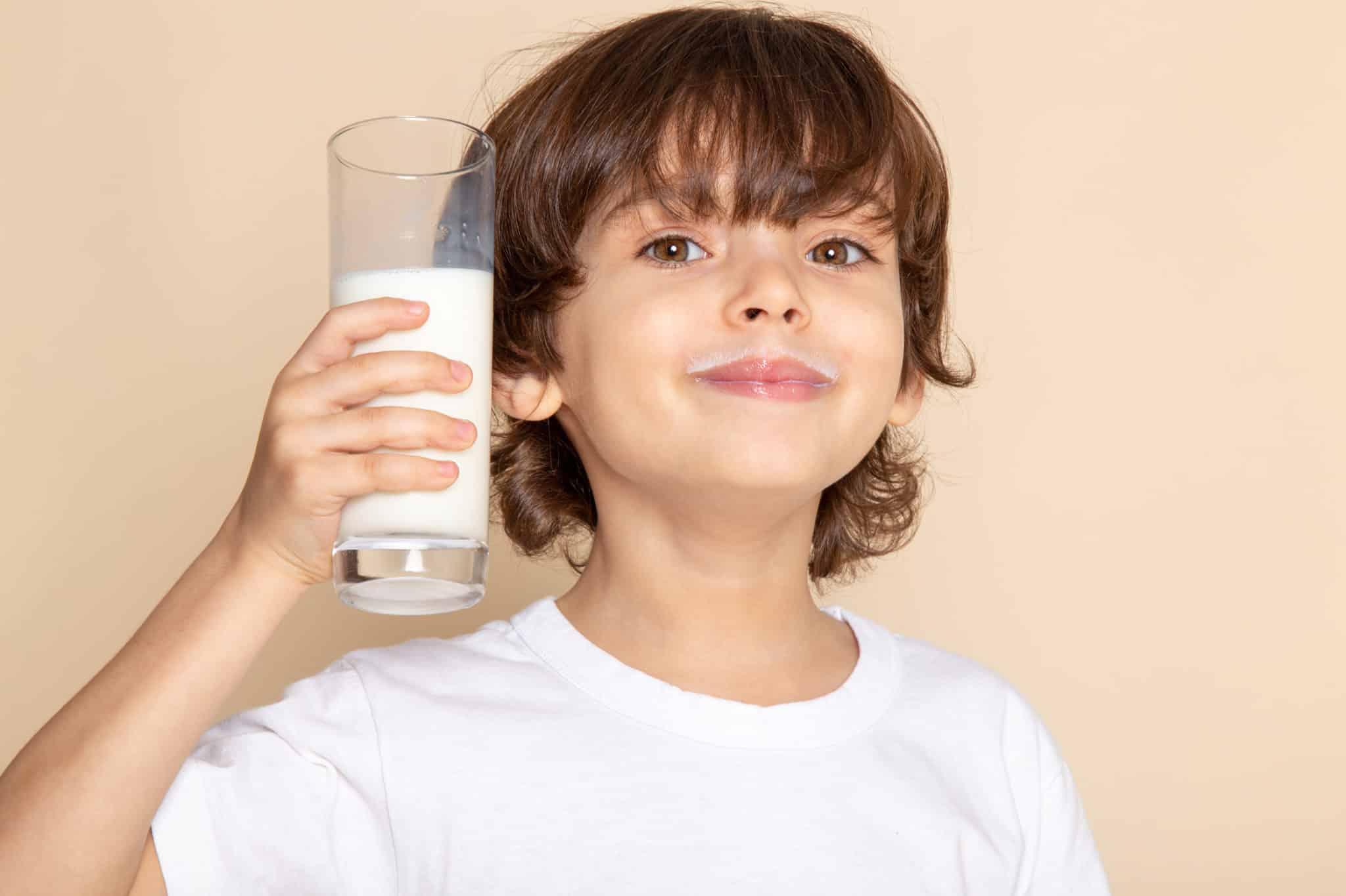 Petit garçon boit un verre de lait avant de dormir